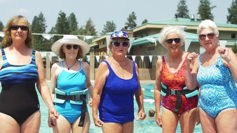 Five adorable old ladies wearing festive bathing suits and sunglasses stand by the pool, and flex their muscles at the camera