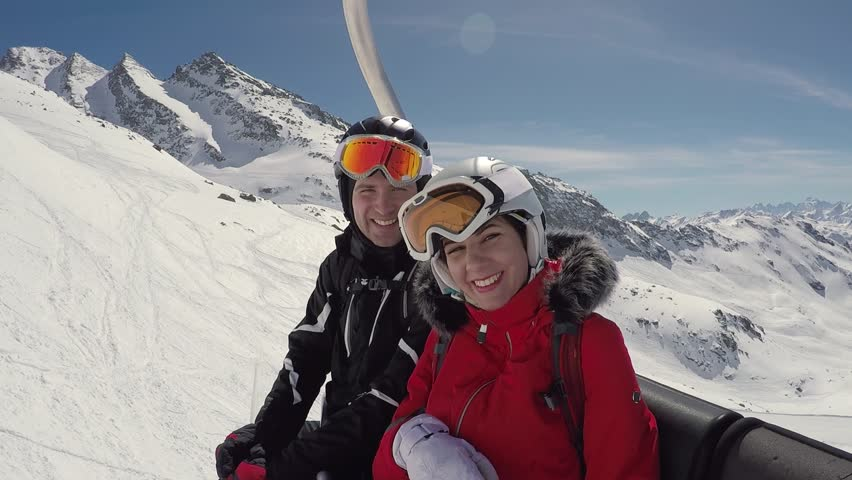 A loving couple of skiers climbs up the mountain on a ski lift, they have fun and are fooling, portraying funny faces on their faces, smile a lot and look at the camera