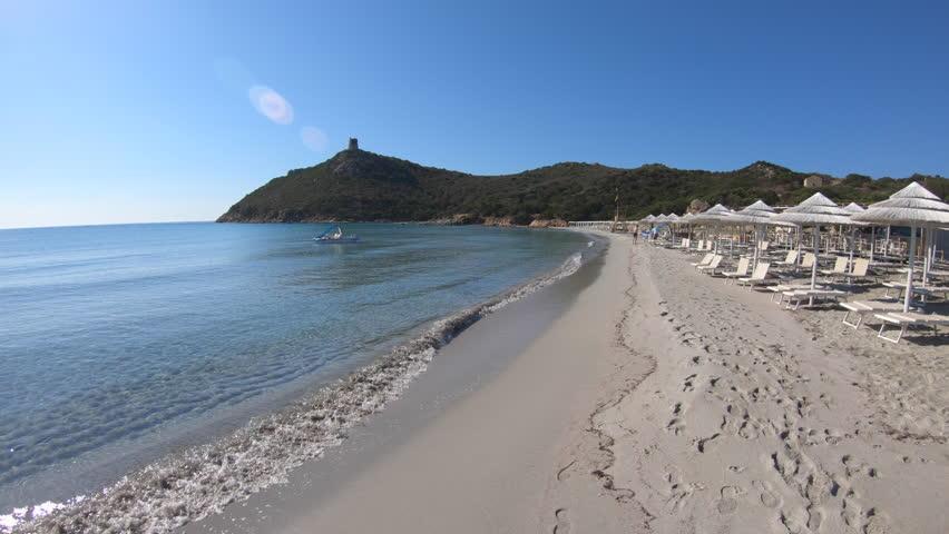 People relaxing on holidays in Italy, families and tourists on summer vacation. Italian coast in Sardinia on Mediterranean Sea. Sandy beach in Porto Giunco, Villasimius, Sardegna, Italia