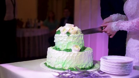 Brides cut wedding cake. A bride and a groom is cutting their wedding cake. Hands of bride and groom cut of a slice of a wedding cake