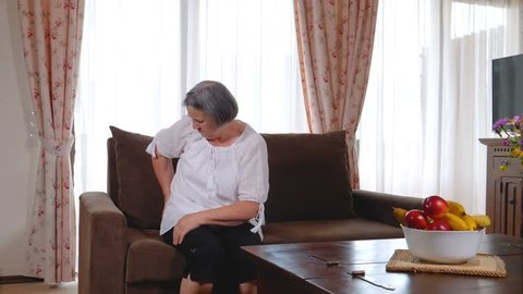 Mature woman suffering from backache at home. Massaging lower back with hands, feeling exhausted, standing in living room. Slow motion 4k