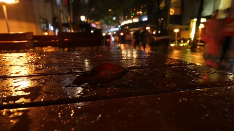Closeup time lapse shot of fallen leaf on wet table of outdoor restaurant, people figures rush at passage, seen blurred on background. Dark Xintiandi area at night time