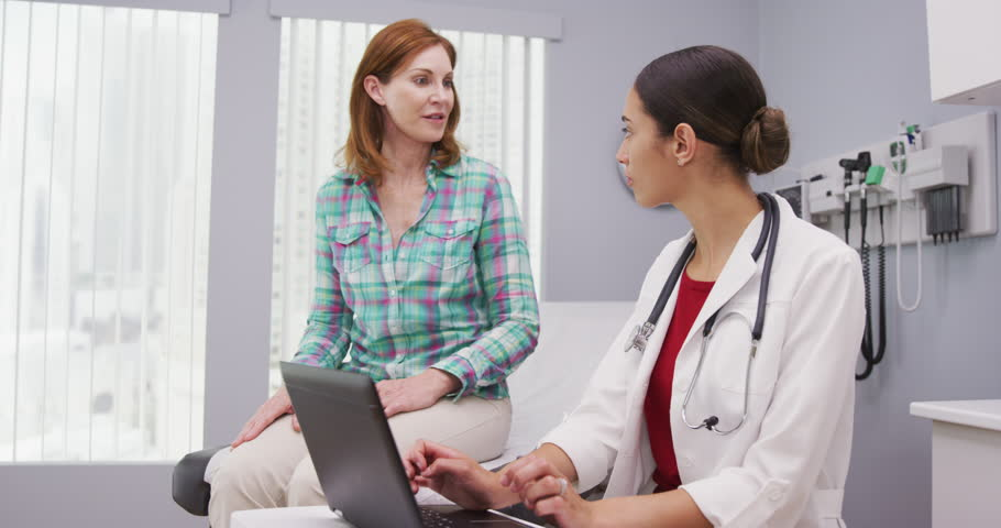Portait of young latina doctor using laptop computer while talking with senior patient inside clinic. Close up of middle aged patient discussing with young female doctor health issues | Shutterstock HD Video #1015761151