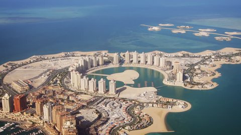 Passenger window view of Pearl Qatar. an artificial island. with its modern. highrise architecture. from a commercial airliner. FullHD footage