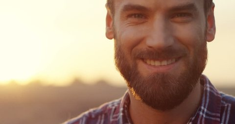 Close up of the Caucasian good looking young man with a beard smiling to the camera and then looking down early in the morning at his field. Portrait.