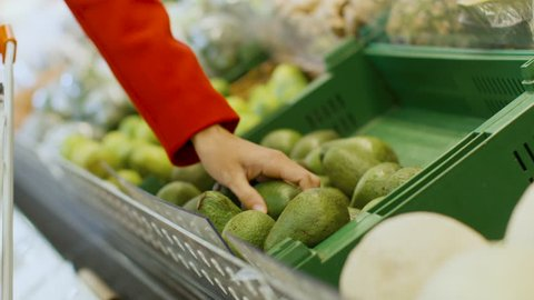 At the Supermarket: Close-up Shot of the Woman's Hand Taking Avocado from the Fresh Produce Section and Places it into Shopping Cart. Shot on RED EPIC-W 8K Helium Cinema Camera.