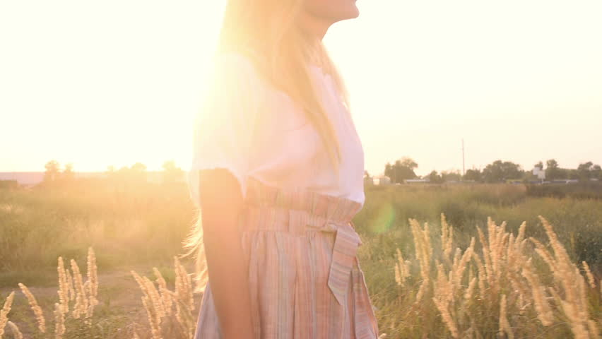 Beautiful girl with long blonde hair in white blouse walking on field at sunset  #1015808611
