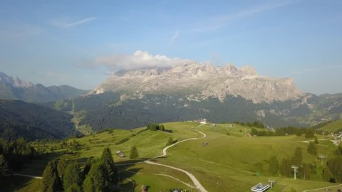 Aerial drone landscape at the meadows at high altitudes, forming gentle hills. Sella massif in the background. Dolomites, Alta Badia, Sud Tirol, Italy