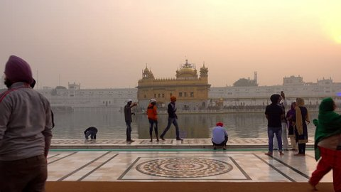 AMRITSAR - PUNJAB - INDIA - 13 NOVEMBER 2017 - Video of Sikh pilgrims in the Golden Temple at sunset during celebration day. Harmandir Sahib is the holiest pilgrim site for the Sikhs.