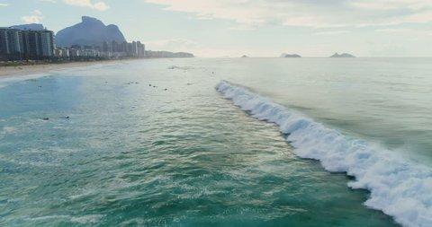 Aerial above the ocean with surfers, Barra da Tijuca Beach, sunny summer morning in Rio de Janeiro, Brazil