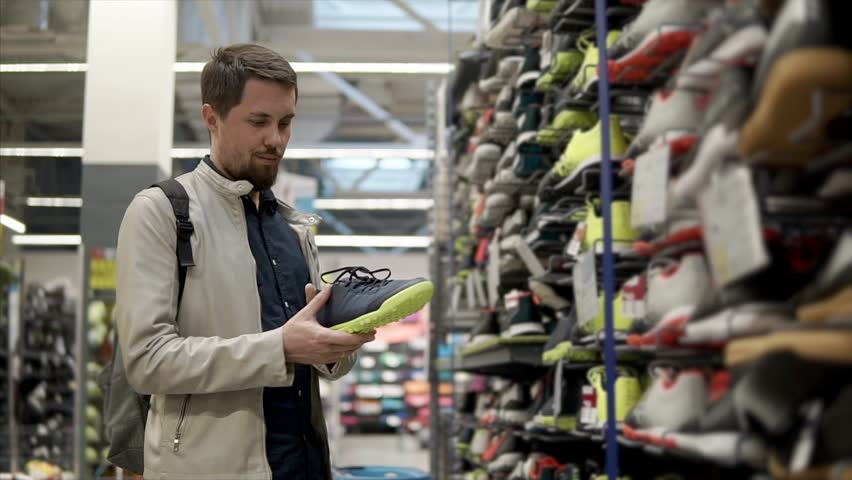 Man shopper is watching pair of shoes in sport store. He is checking quality and taking second sneaker from shelf, thinking about buying | Shutterstock HD Video #1015886701