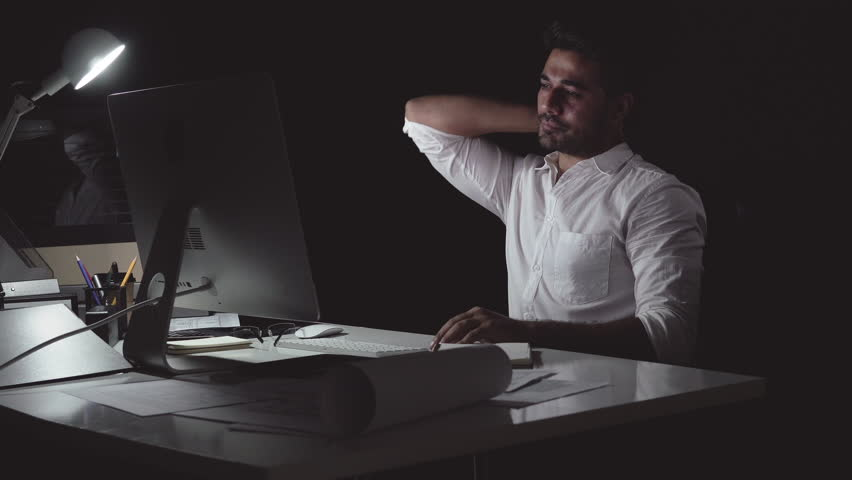 Workaholic Asian businessman working on computer late at night in the office feeling tired and having back pain from overwork