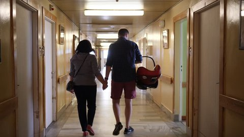 Parents with newborn baby in a car chair leavin the maternity hospital walk down the hall