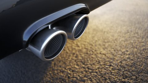 Sports car chrome exhaust in close up symbolizing automobile performance, power, durability and carbon dioxide pollution levels. Vehicle standing on an asphalt road during sunset on a clear weather.