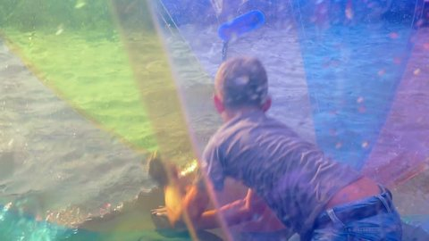 school age boy having fun in a large semi-transparent inflatable plastic ball that floats in water