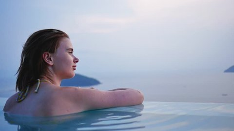 Red-haired girl in swimming-pool watching ocean