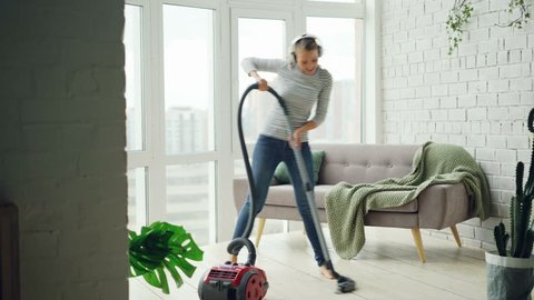 Beautiful woman is hoovering the floor at home using modern vacuum cleaner and listening to music with headphones, dancing and singing. Housework and technology concept.