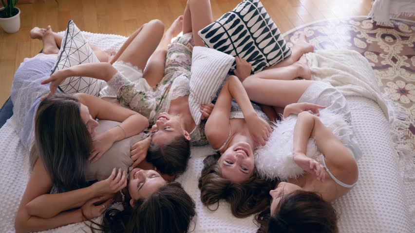 pajama party, happy friends in sleepwears gossip with pillows lying on the bed in slow motion