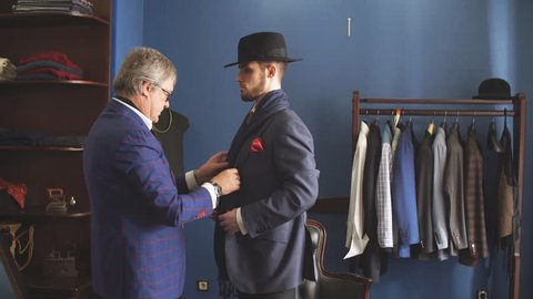 Young, handsome and successful businessman trying on a custom made stylish suit at tailors shop. Dressmaking and Tailoring establishment concept