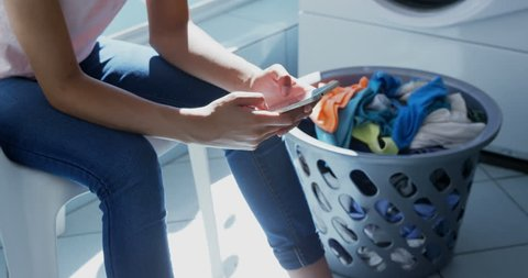 Mid section of woman using mobile phone at laundromat 4k