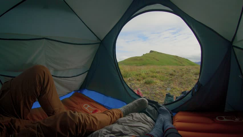 Young travelling tourist nomad couple inside camping tent enjoy lazy morning of adventure lifestyle, man wakes up, goes outside to stretch and enjoy breath of fresh air. iceland exploration #1015936411