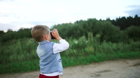 Little boy taking pictures of nature  beautiful baby smiling and holding a  camera  a child with a camera in his hands  the boy learns to photograph a  beautiful child of nature with a camera