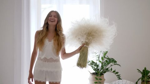 healthy happy girl in pajama jumps with bouquet of feather grasses in cozy atmosphere room, allergy free