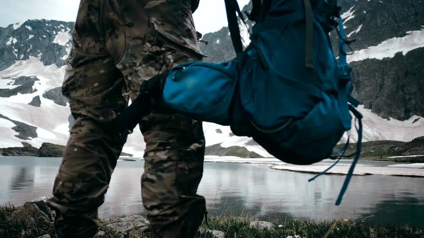 Climber removes a backpack rucksack near a large crystal clear lake on top of a mountain