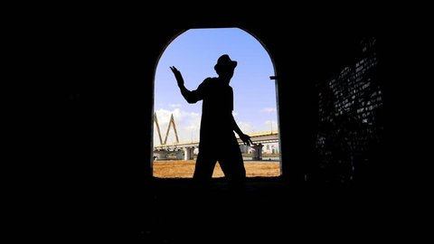 Silhouette of a dancer that resembles Michael Jackson. Athletic man dancing in the style of popping.