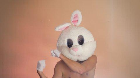Shirtless man dancing with bunny mask, loop