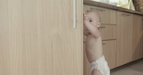 Toddler child in kitchen opens wood cabinet