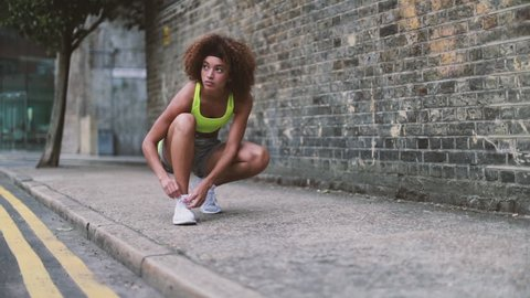 Young adult female tying shoe lace before a run