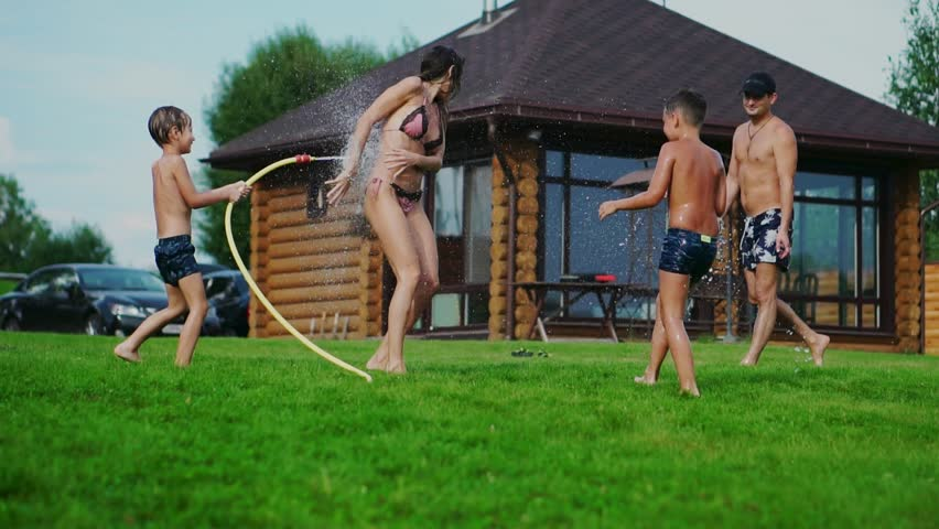 Family in the backyard of a country house in the summer relax playing with water and hosing #1015997251