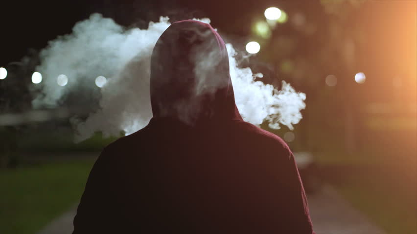 The fellow in a hood walking and smoking on the night street. slow motion