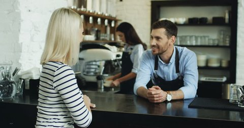 Handsome waiter talking with pretty blonde client at the bar, while waitress serving her coffee.