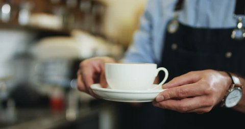 Close upof the cup of coffee being given from man's hands of barmen to the female client at the cafe.