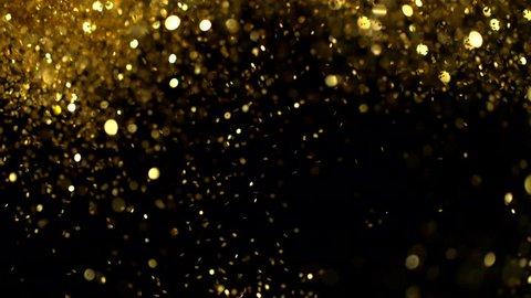 Super slow motion of glittering golden particles on black background. Shallow depth of focus. Filmed on high speed cinema camera, 1000 fps.