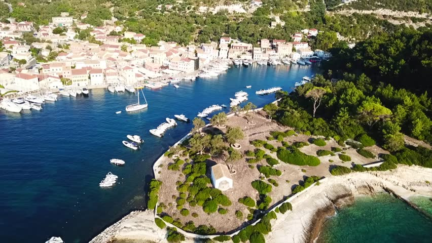 Aerial drone bird's eye view video of iconic small safe port of Gaios with traditional Ionian architecture and sail boats docked, Paxos island, Ionian, Greece | Shutterstock HD Video #1016045851