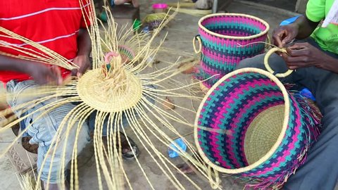 African Art. Men weave baskets and hats in a marketplace in Ghana.