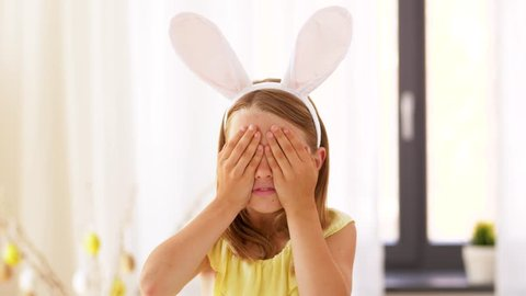 easter, holidays and people concept - happy girl wearing bunny ears headband playing peek a boo game at home