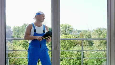 attractive Construction worker makes measurements of windows using measuring tape and make notes in tablet. service man installing window
