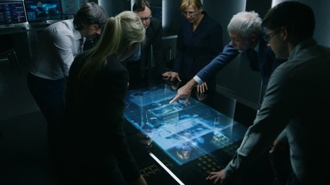 Team of Government Intelligence / FBI Agents Standing Around Digital Touch Screen Table and Tracking Suspect Vehicle Using Satellite Surveillance in the Monitoring Room. Shot on RED EPIC-W 8K Camera.