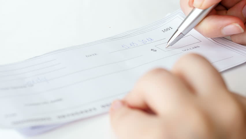 Closeup 4k video of businesswoman filling one thousand dollar bank cheque with pen