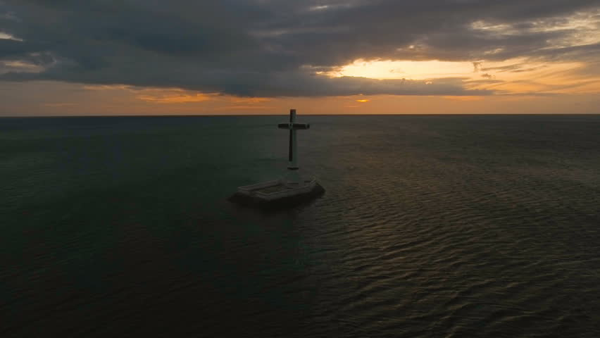 Aerial view Sunken Cemetery cross in Camiguin Island, Philippines,sunset. Large crucafix marking the underwater sunken cemetary of the coast of camiguin island near mindanao in the Philippines