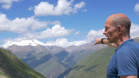 close bold man in t-shirt talks pointing to pictorial canyon between high mountains against snowy tops under blue sky