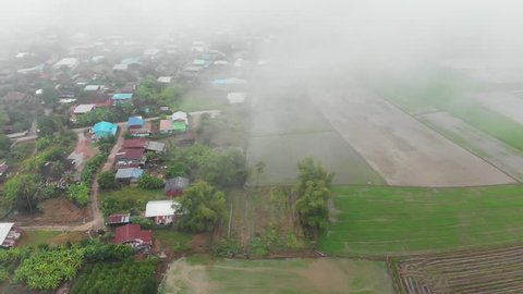 Aerial View of Mist on Rice Field, Rural Village and Agricultural Area in Phitsanulok Province, THAILAND