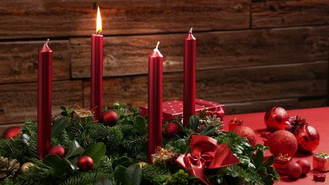 One burning red candle on a traditional advent wreath of green fir twigs and mistletoes with festive decoration in front of a rustic wooden wall, close-up real time shot with copy space, nobody