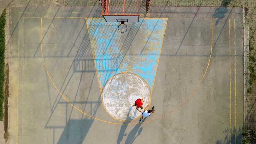 Aerial view of two young friends playing basketball on court outdoors. | Shutterstock HD Video #1016104951
