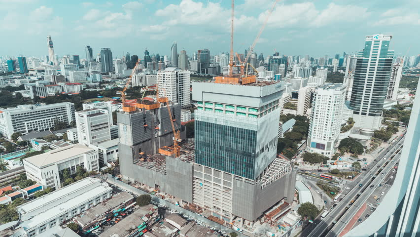 4k UHD day to night holy grail time-lapse of building construction site in city, end with traffic light trails and rain, aerial cityscape view. Construction industry or Asia developing country concept | Shutterstock HD Video #1016120701