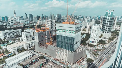 4k UHD day to night holy grail time-lapse of building construction site in city, end with traffic light trails and rain, aerial cityscape view. Construction industry or Asia developing country concept